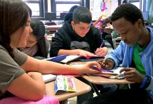 Four students, desks in a circle, working as a group; one helping another with a math problem