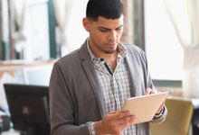 A young man in a checkered button up shirt and a gray sweater is standing in a classroom, holding and looking down at a silver tablet.