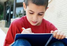 A young boy in a red shirt is sitting outside with a building behind him. His knees are up close to his chest with a with a blue notebook resting against them. He's smiling, writing in his notebook.