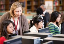 A librarian is peering over the shoulder of a student who is sitting next to two other female students, all working on desktop computers in a library.