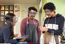Students in high school science class do an experiment with help from tablet