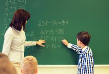 Elementary school teacher works with student on math problem on chalk board in classroom