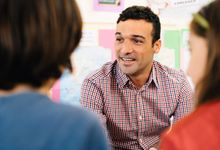 Teacher works with elementary students in class
