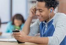 Teen boy listens to headphones