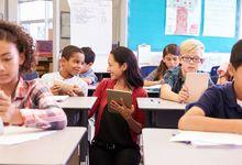 Teacher speaking with student in elementary school classroom