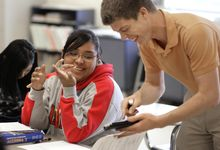 Middle school math teacher works with student to solve problem