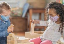 Pre-school children play with blocks wearing masks