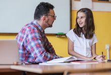 A teacher and elementary school student speak at the teacher's desk