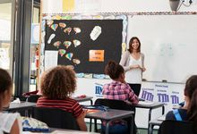 Elementary school teacher teaching students in classroom