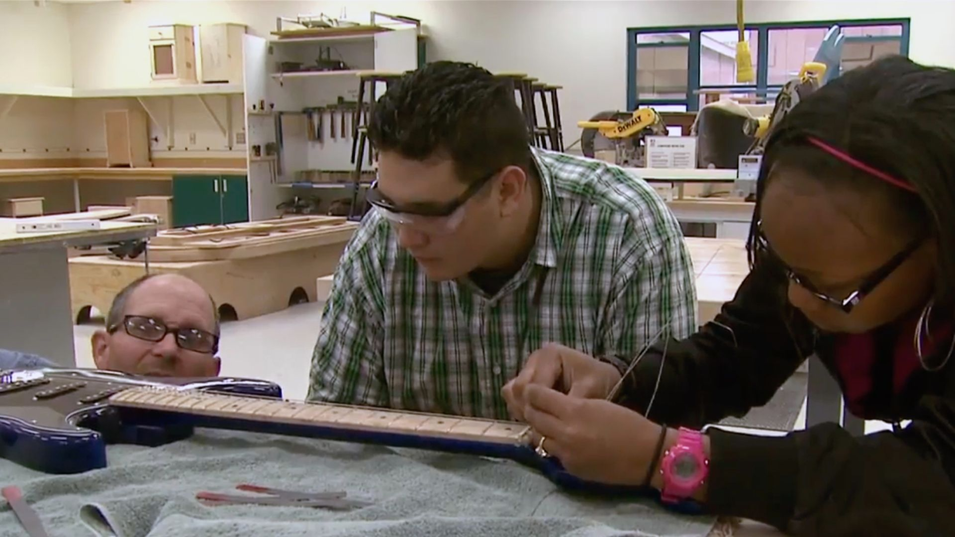 Teacher and students are working on a guitar.