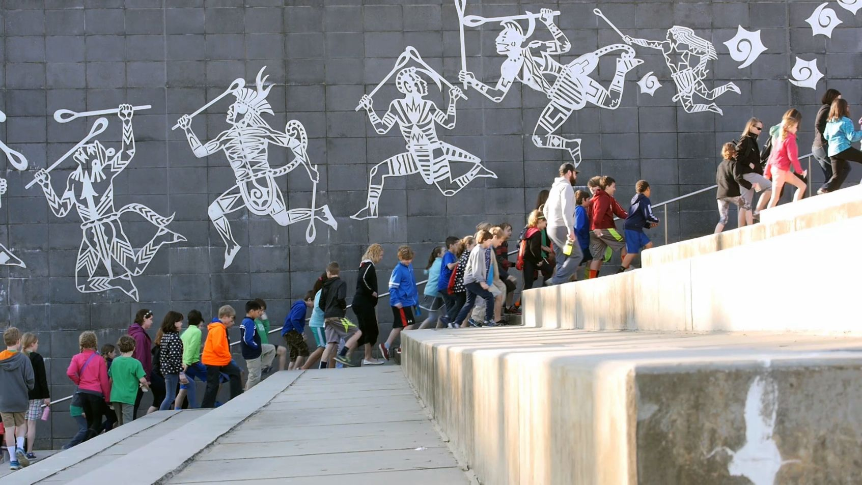 Students and teachers are walking by an art wall.