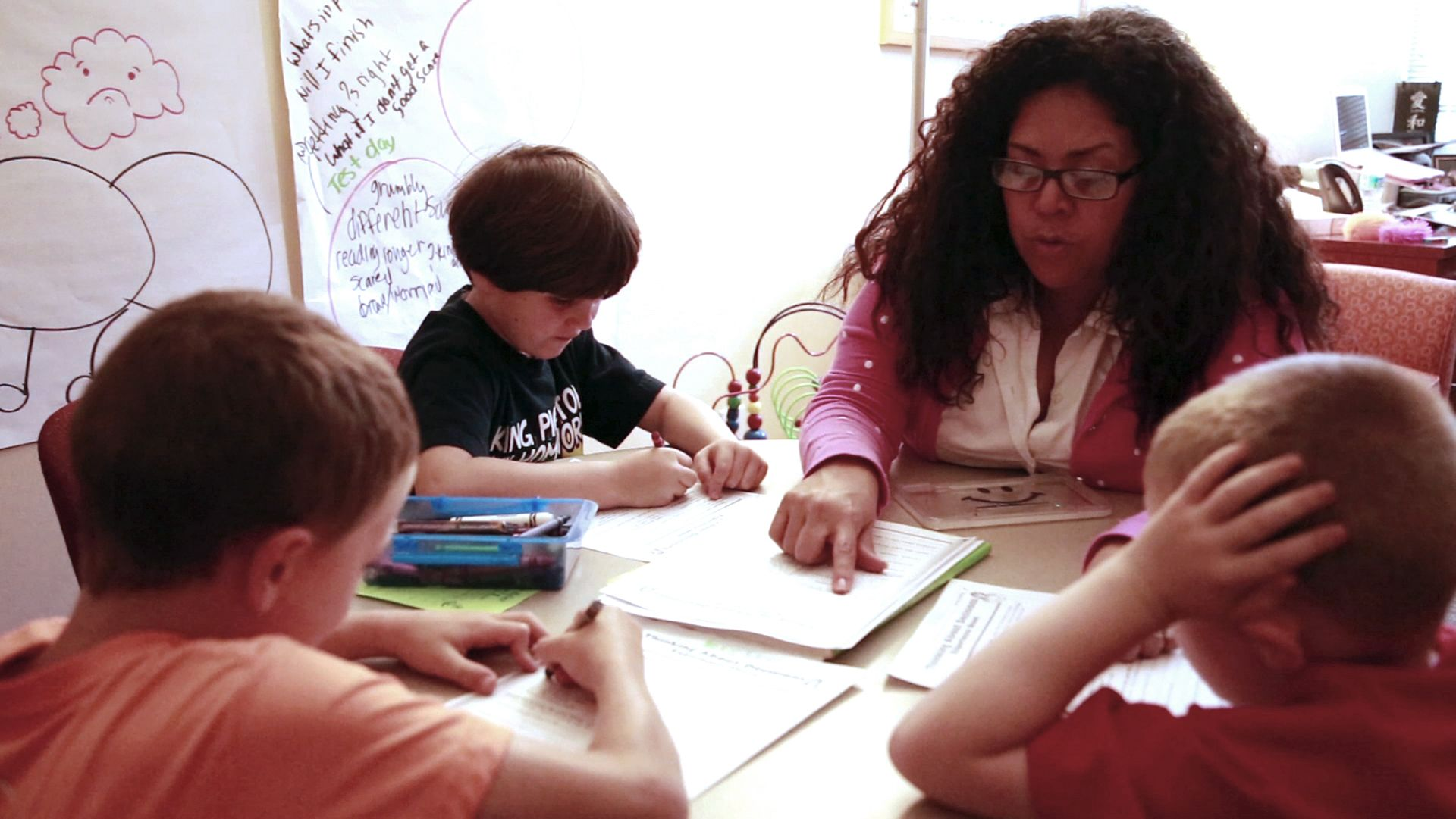 Teacher and a group of students are working together in a classroom.