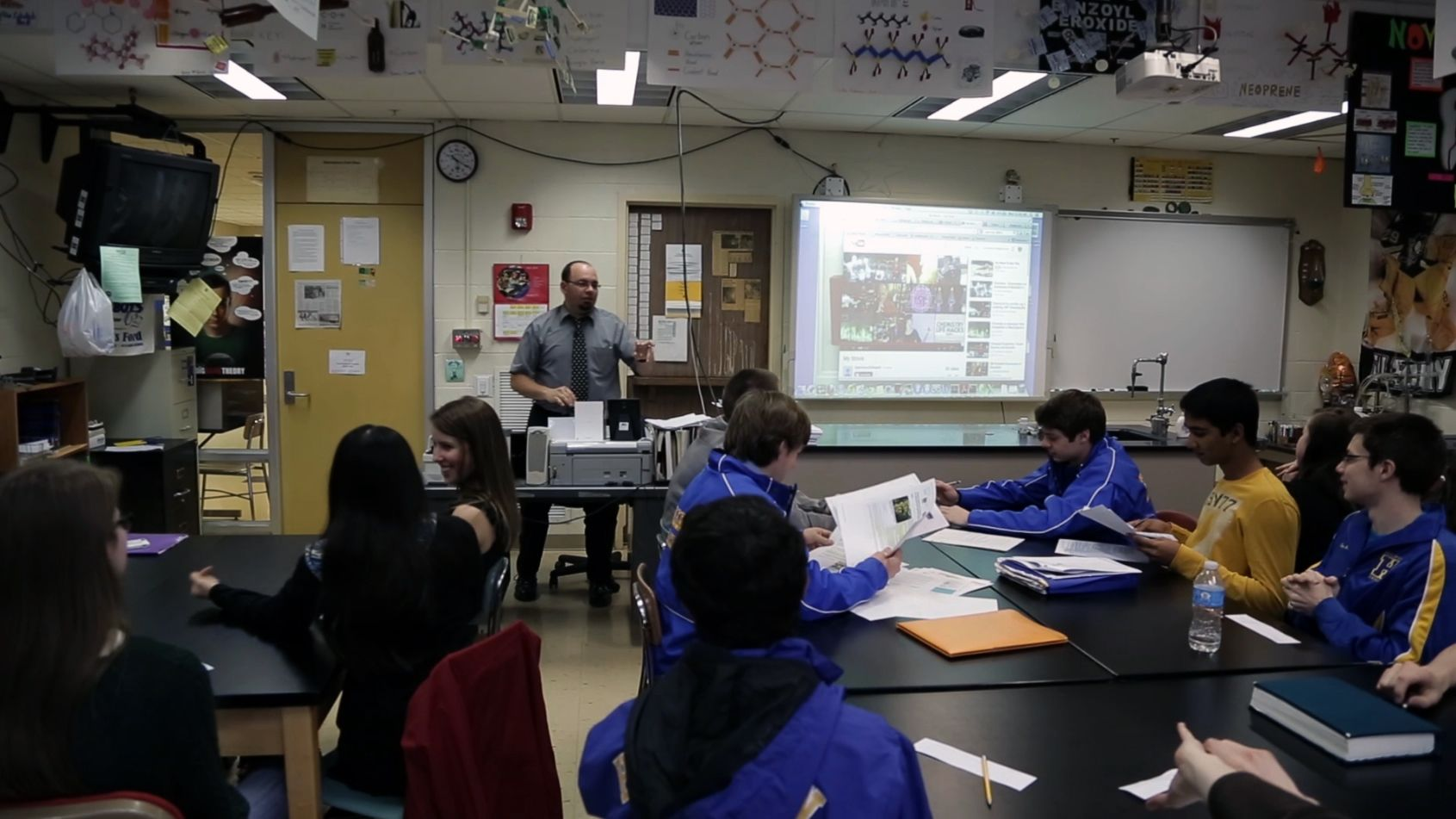 A classroom full with students and a teacher. Teacher is teaching the students with the presentation in front of the classroom.