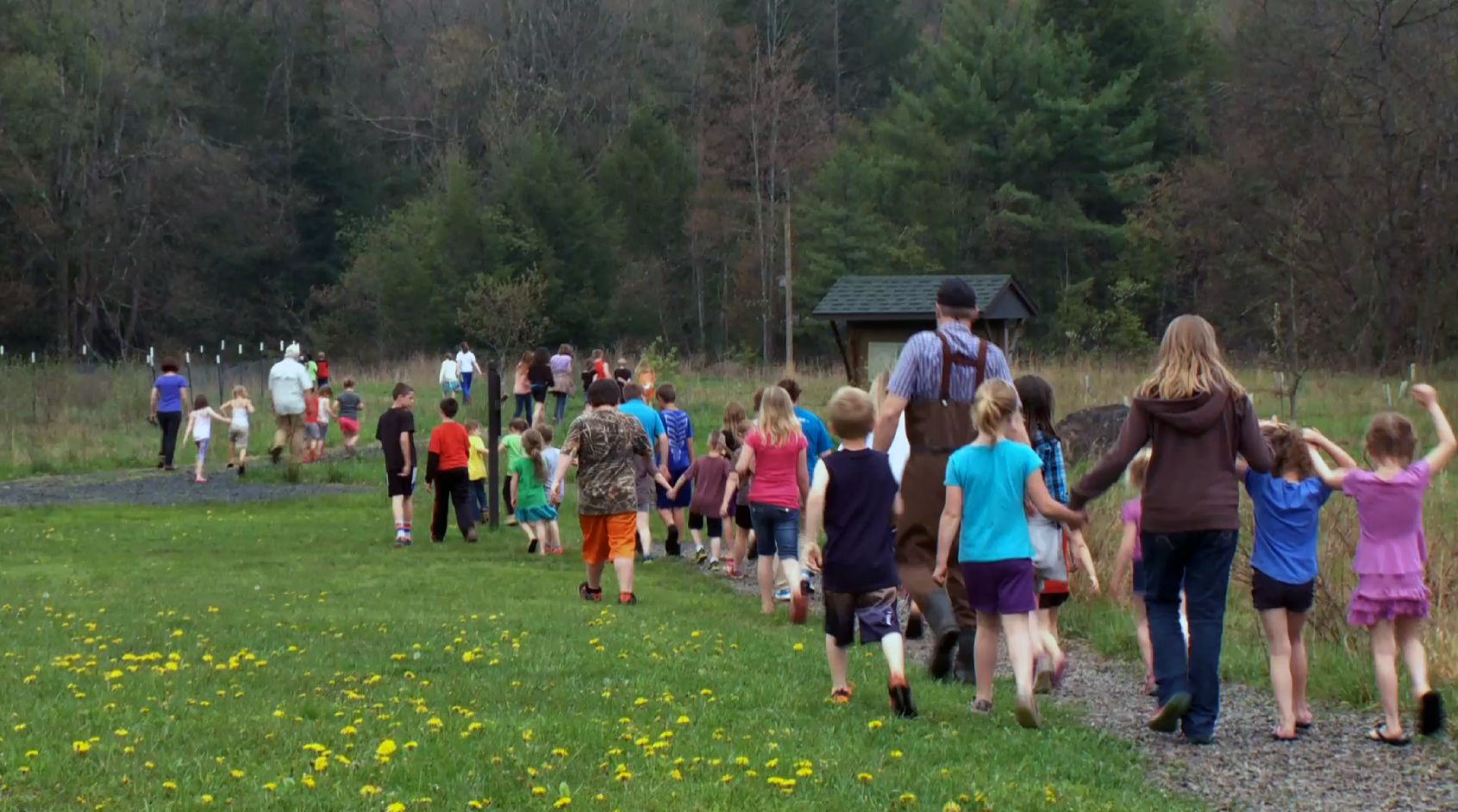 Group of teacehrs and students are on a field trip. They're walking in a green field.