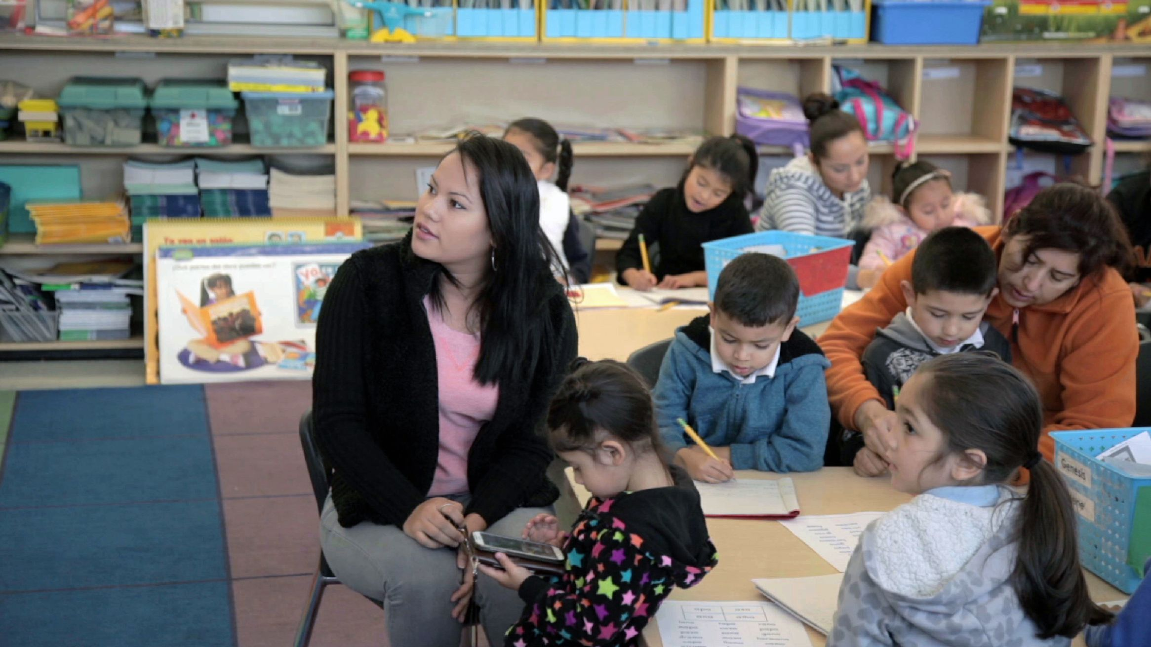 Teacher is teaching a group of primary students in a classroom.