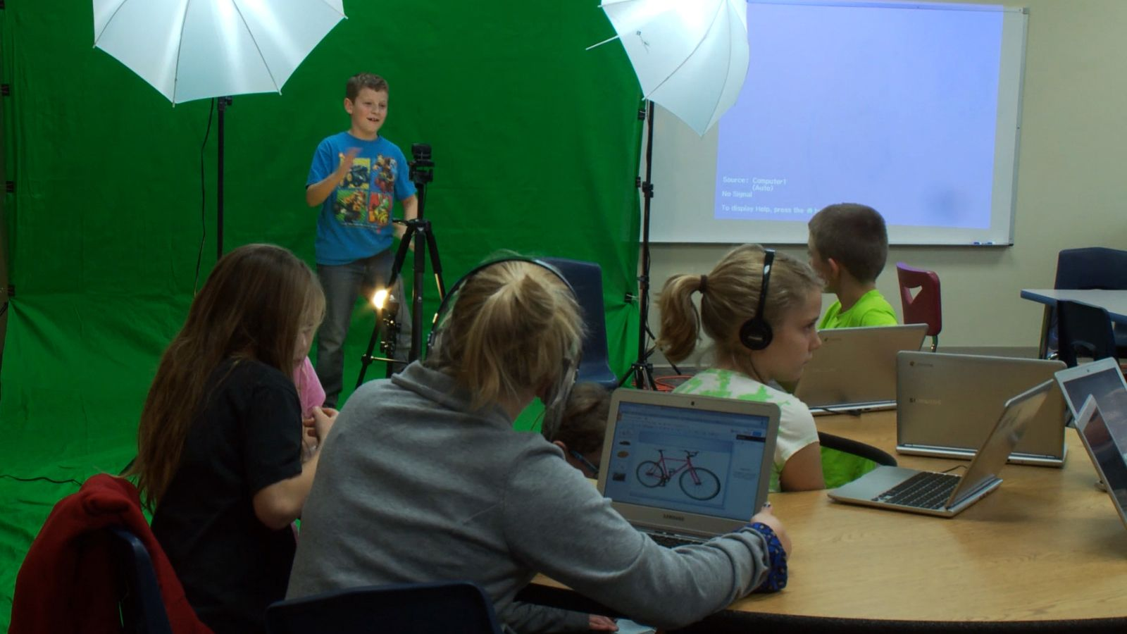 Students are working in a Multimedia class. A student is on a green screen background.