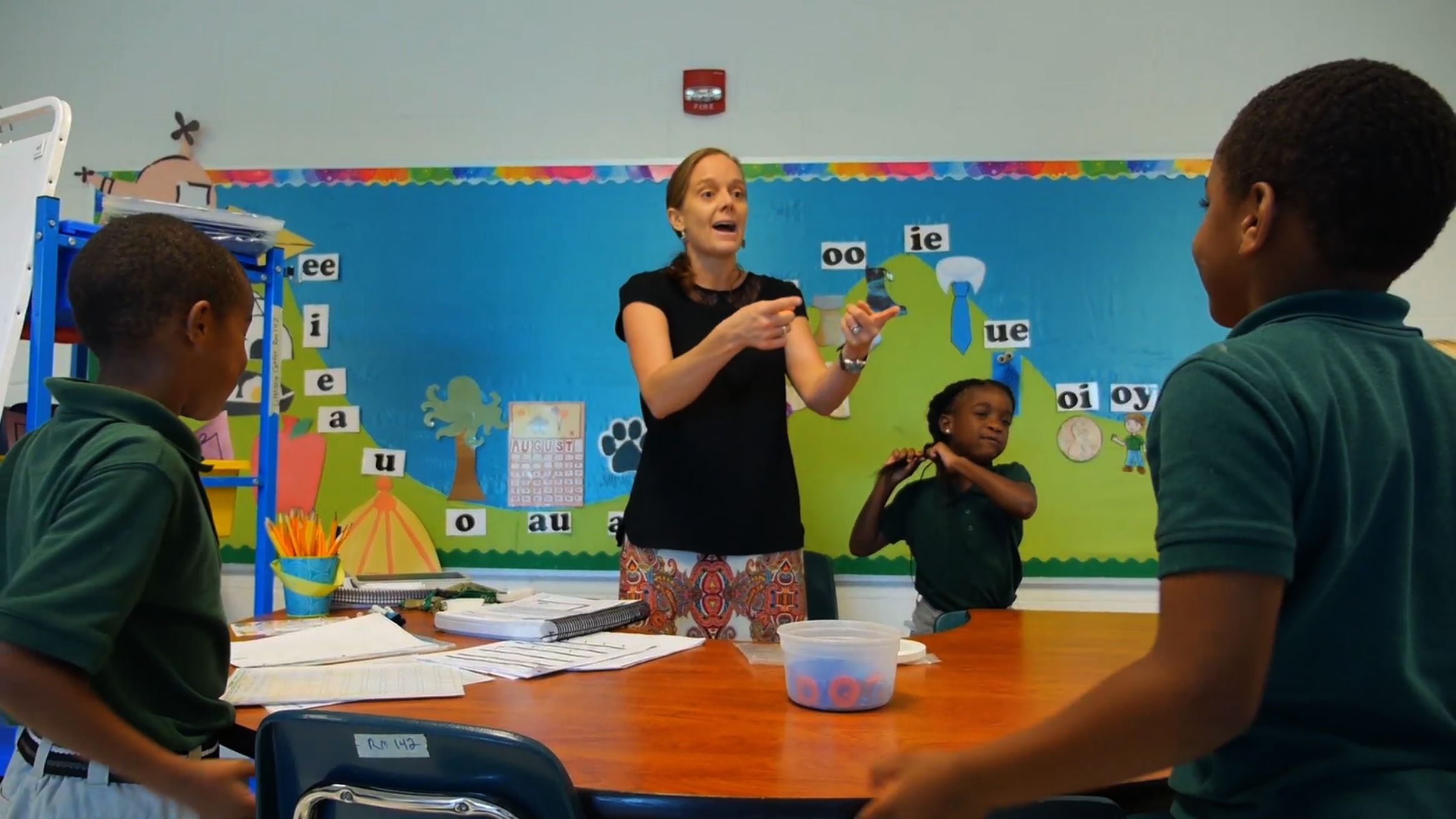 A teacher is working with her primary students in a classroom.