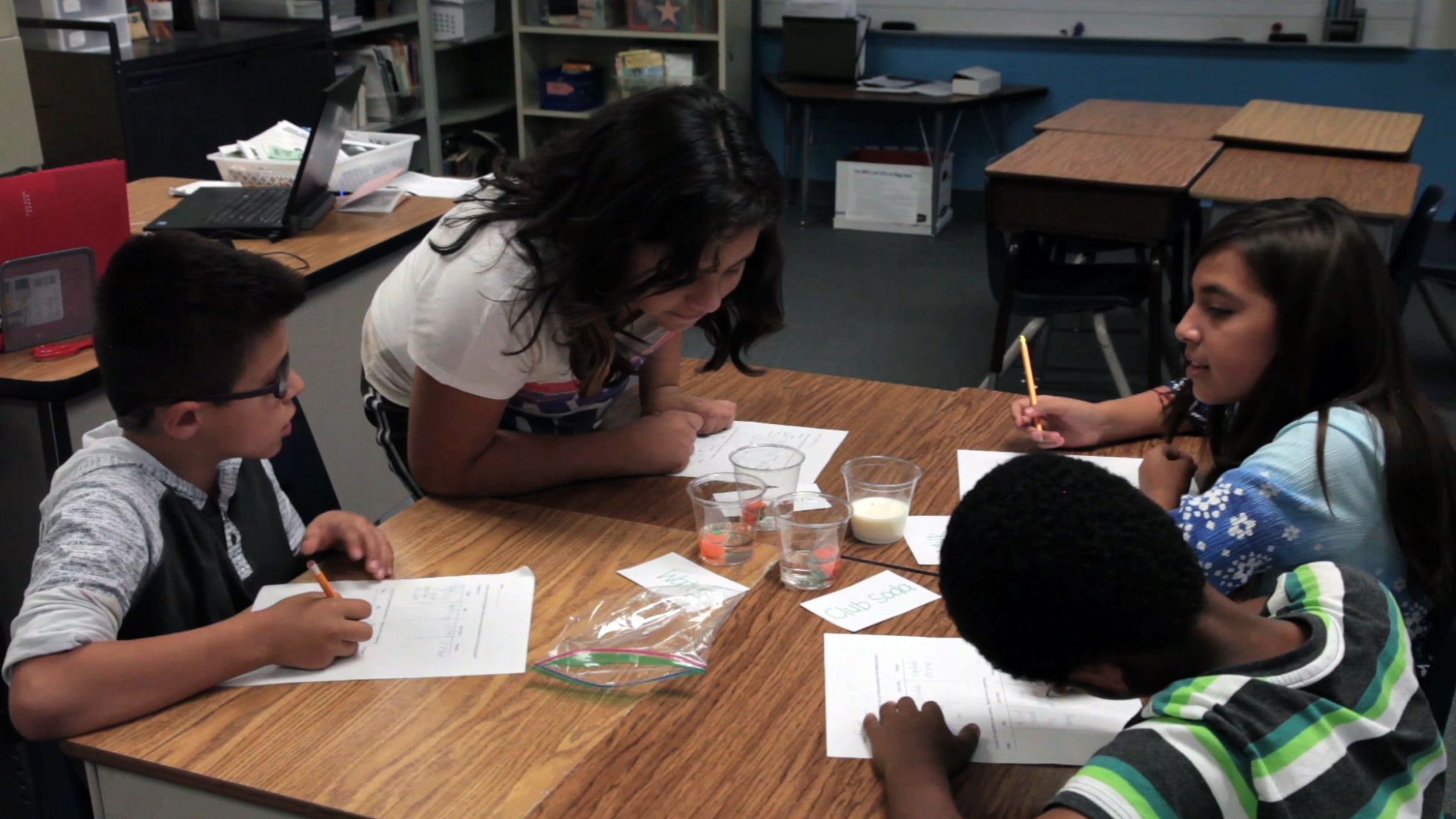 Students are observing on their work in the science class.