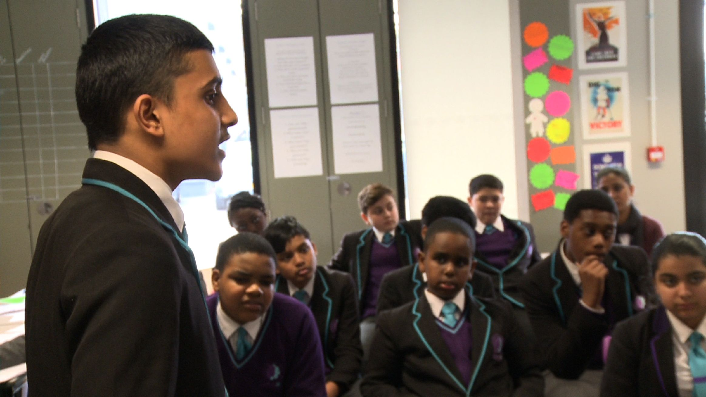 A student is speaking in front of the classroom.