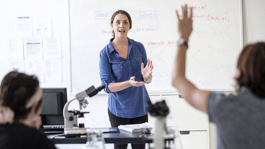 A teacher in a science classroom talks as a student raises their hand.