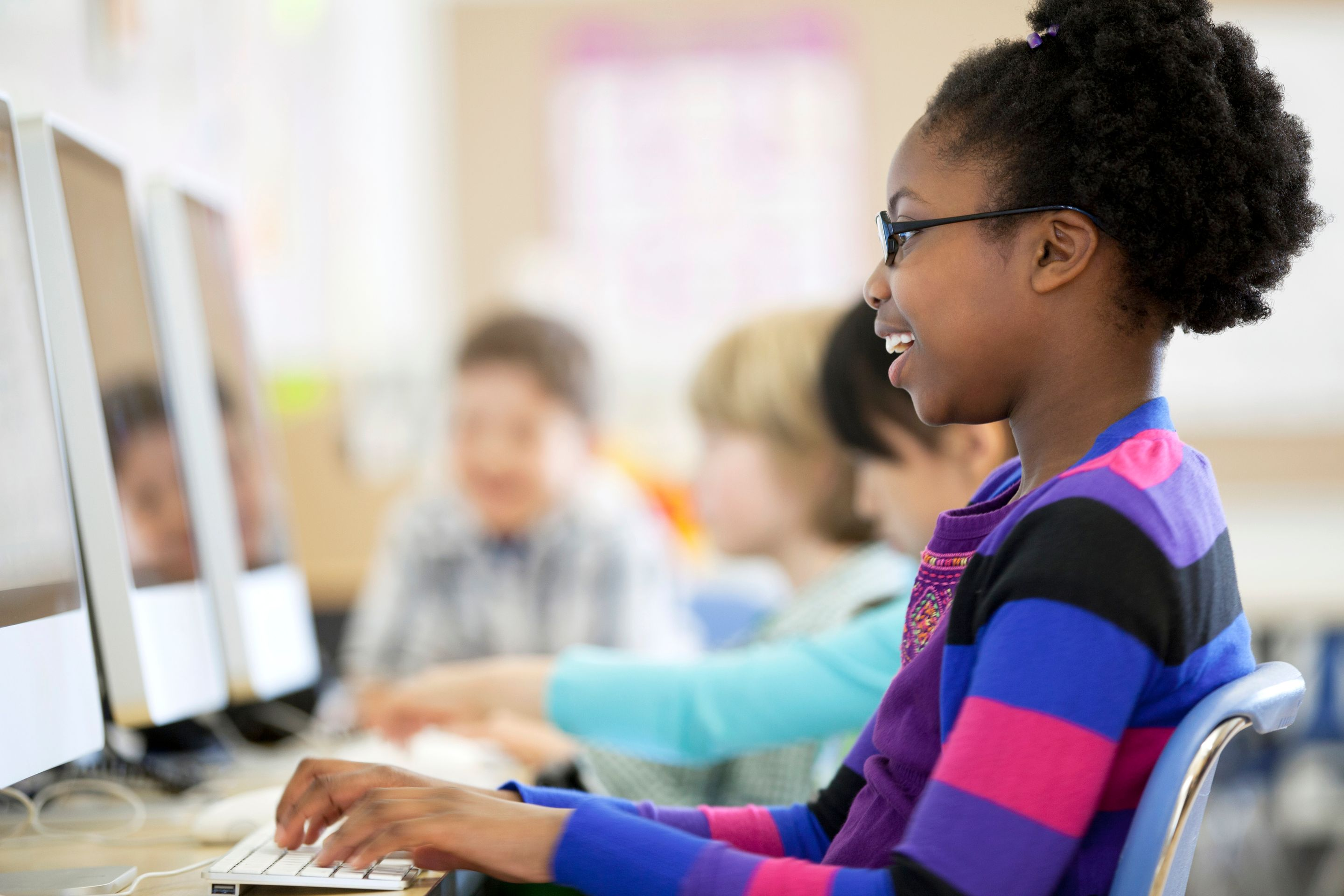 Young African American girl smiling while typing on computer keyboard.