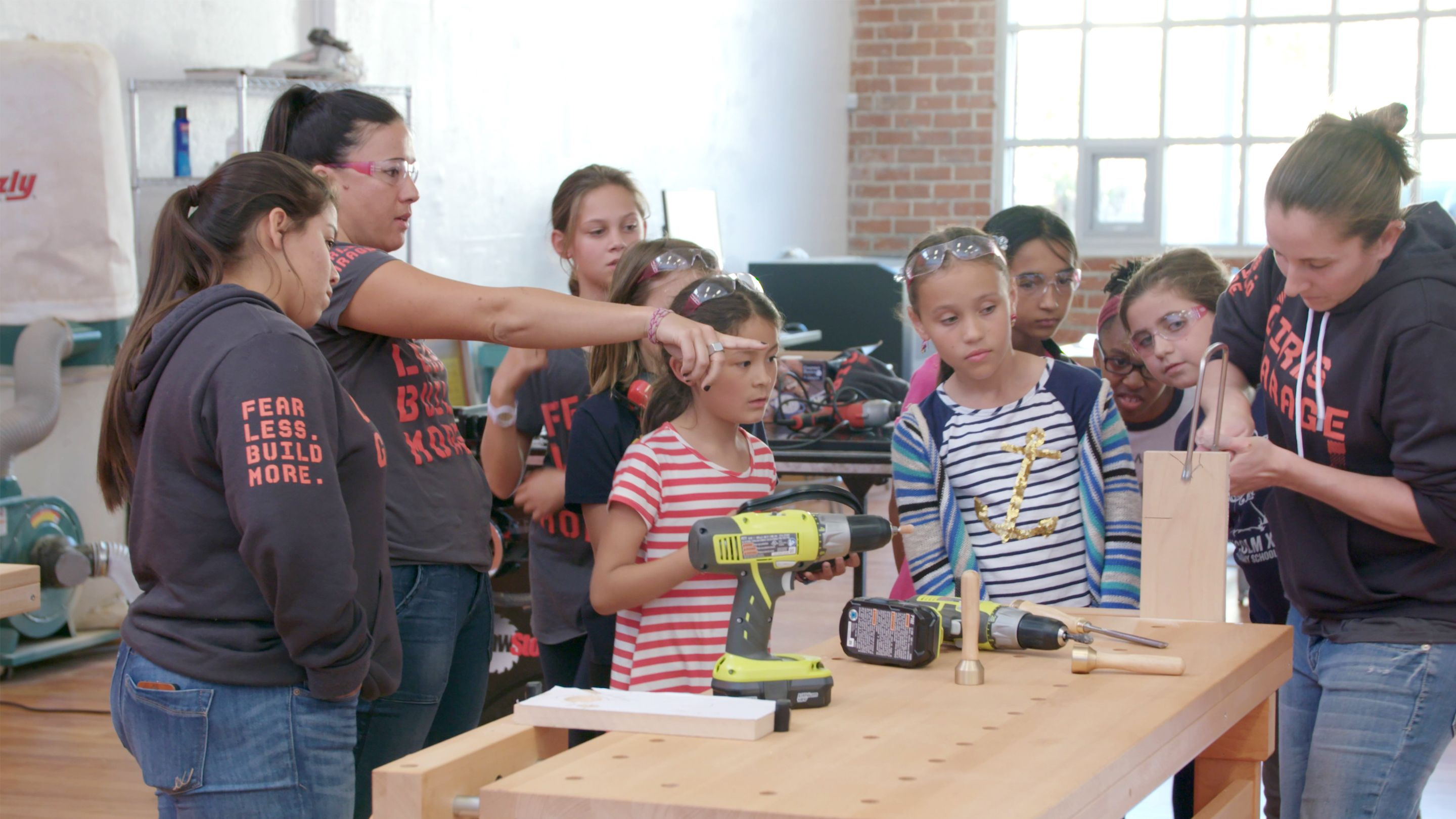 photo of students learning to use tools around a workbench