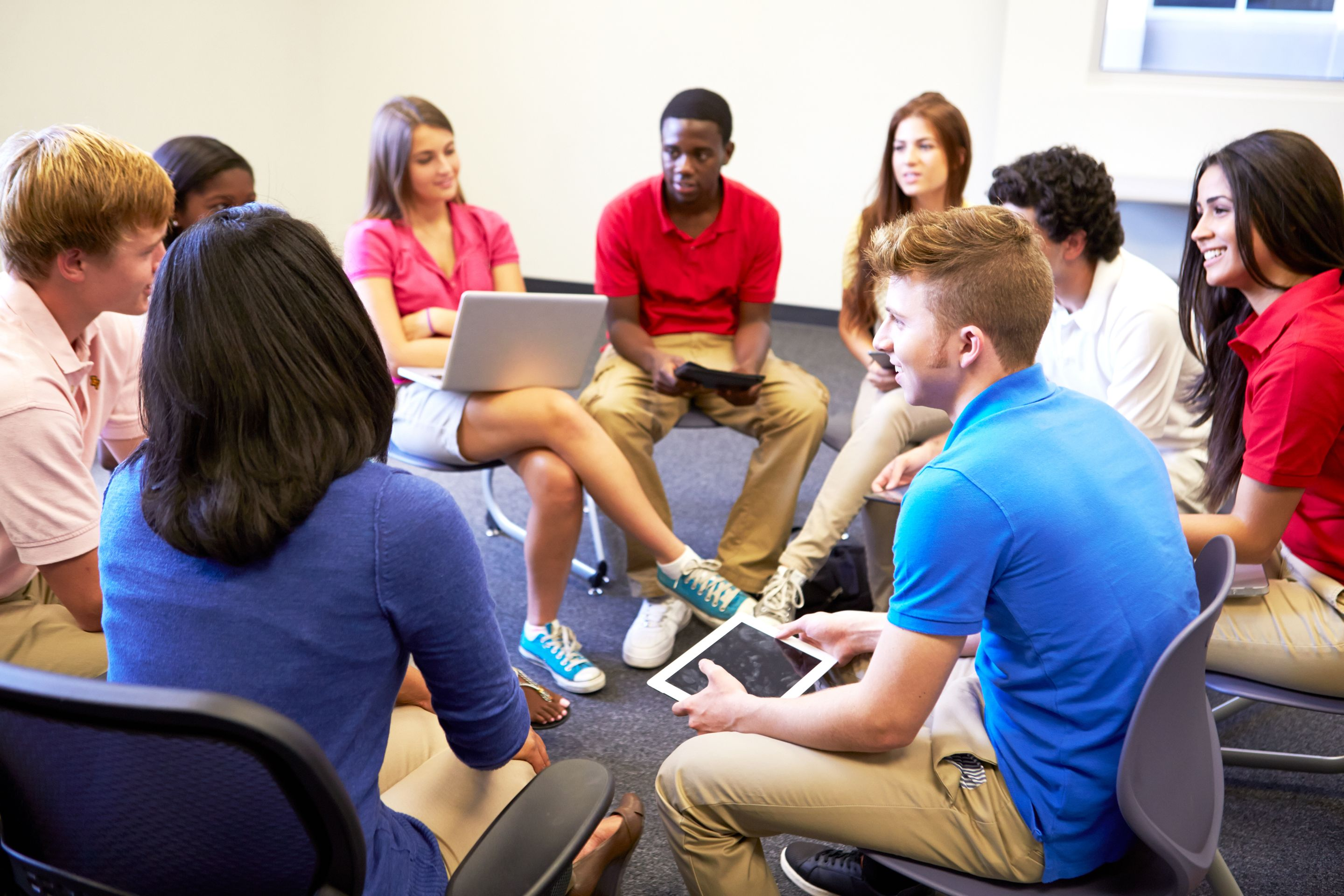 High school students sitting in a circle and taking part in a group discussion.
