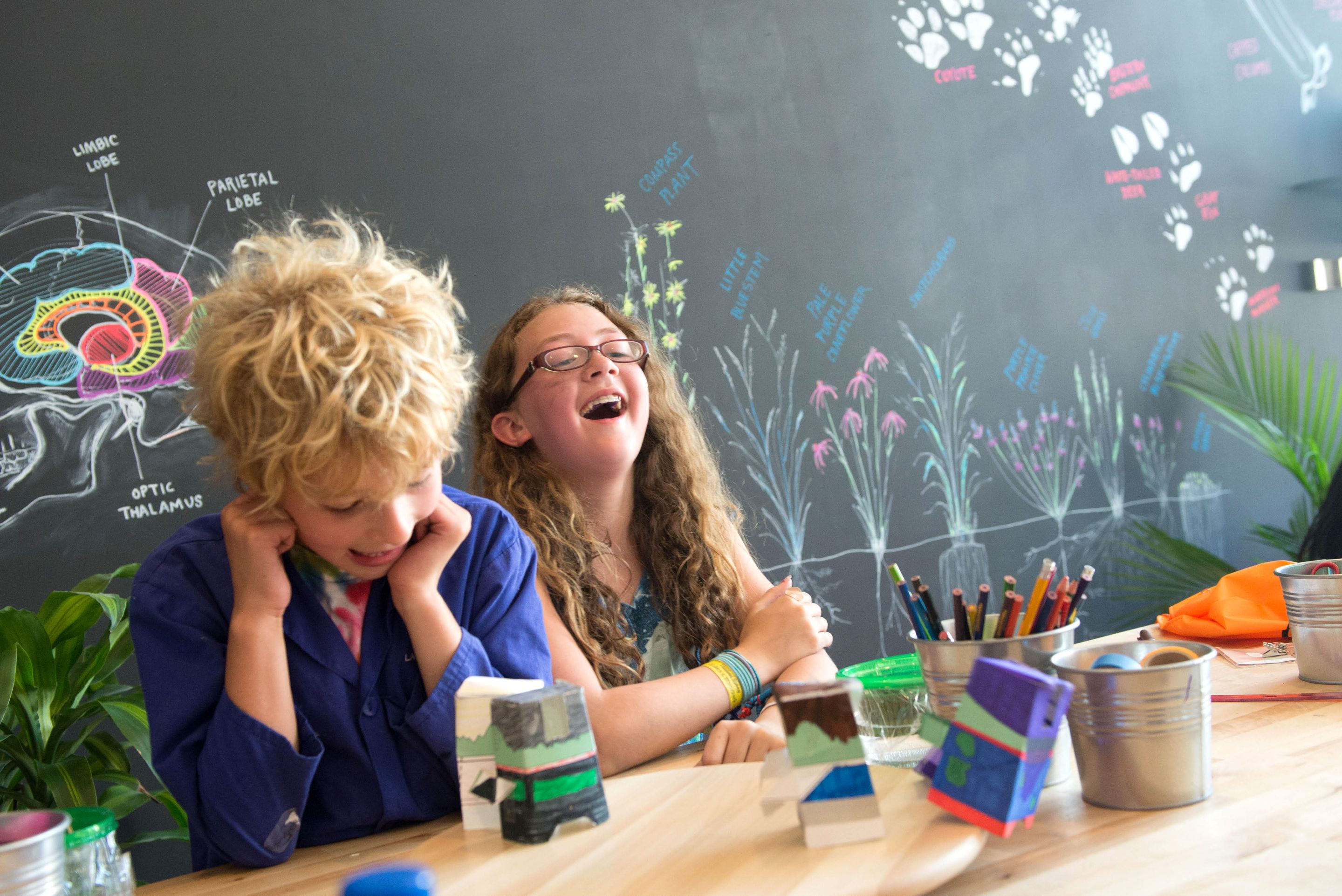 Two students laughing at a table while working on a science project.
