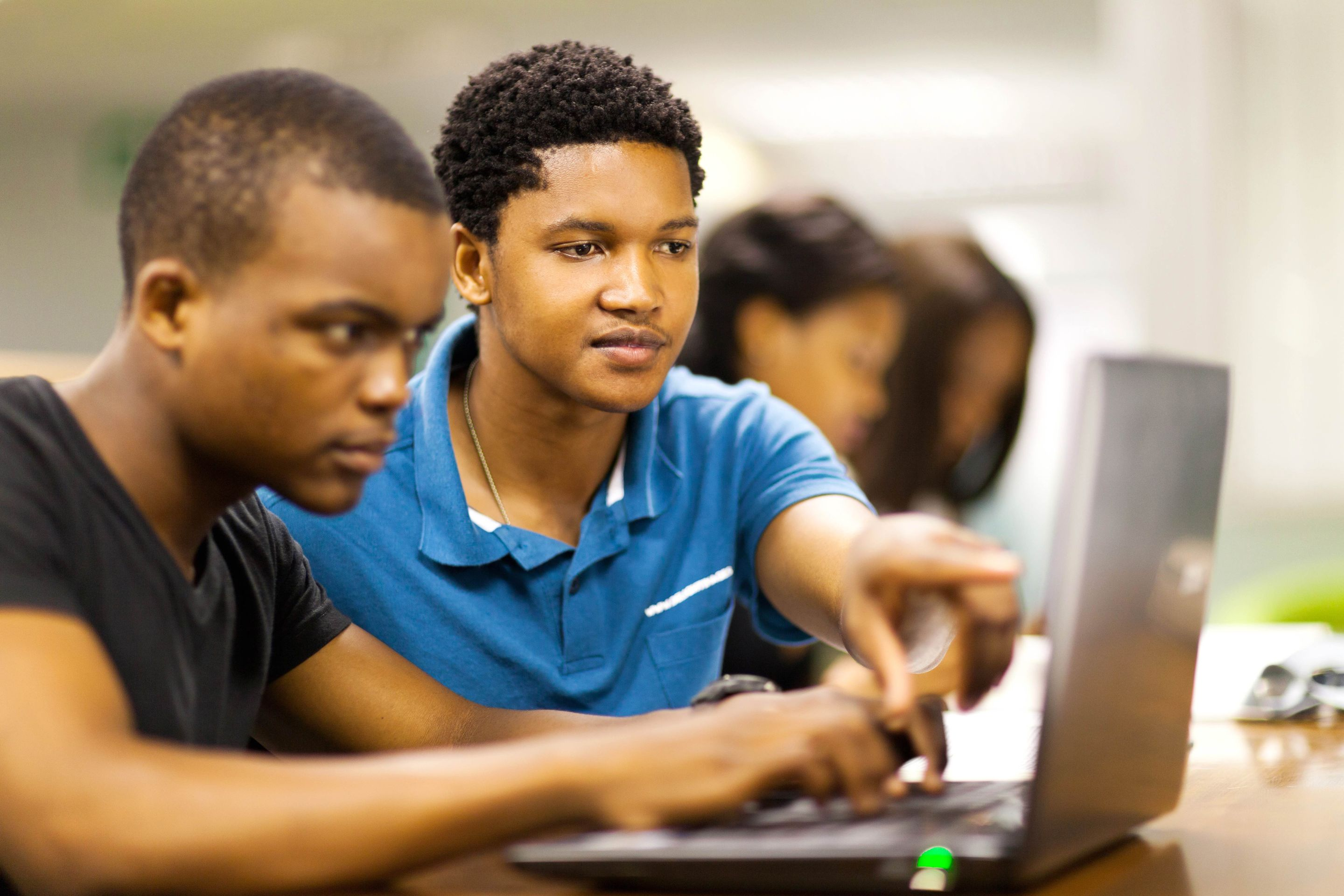 Two high school students using a laptop together.