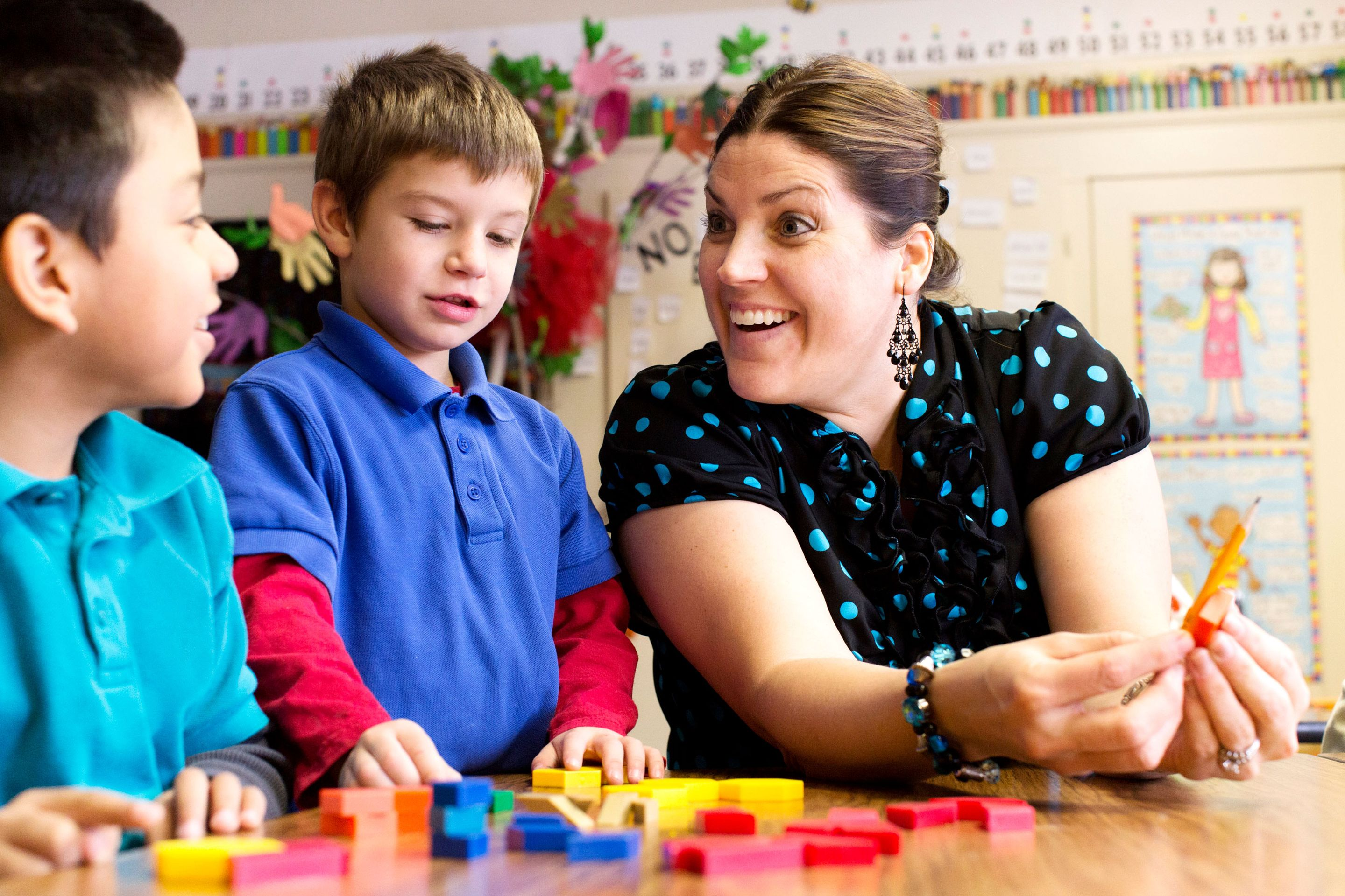 Smiling elementary teacher counting with two students in the classroom.