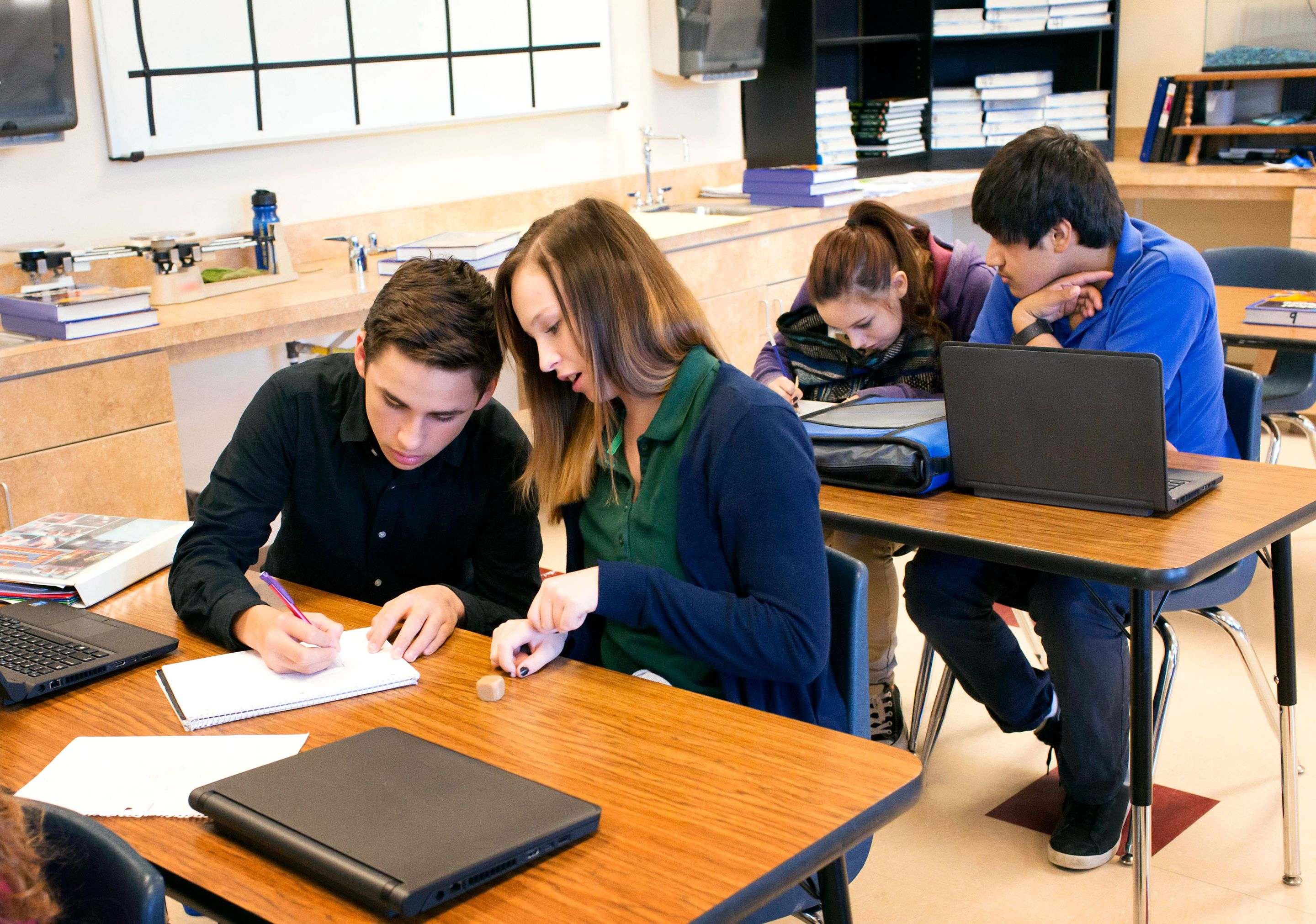 Teenage students working in pairs on a class assignment.