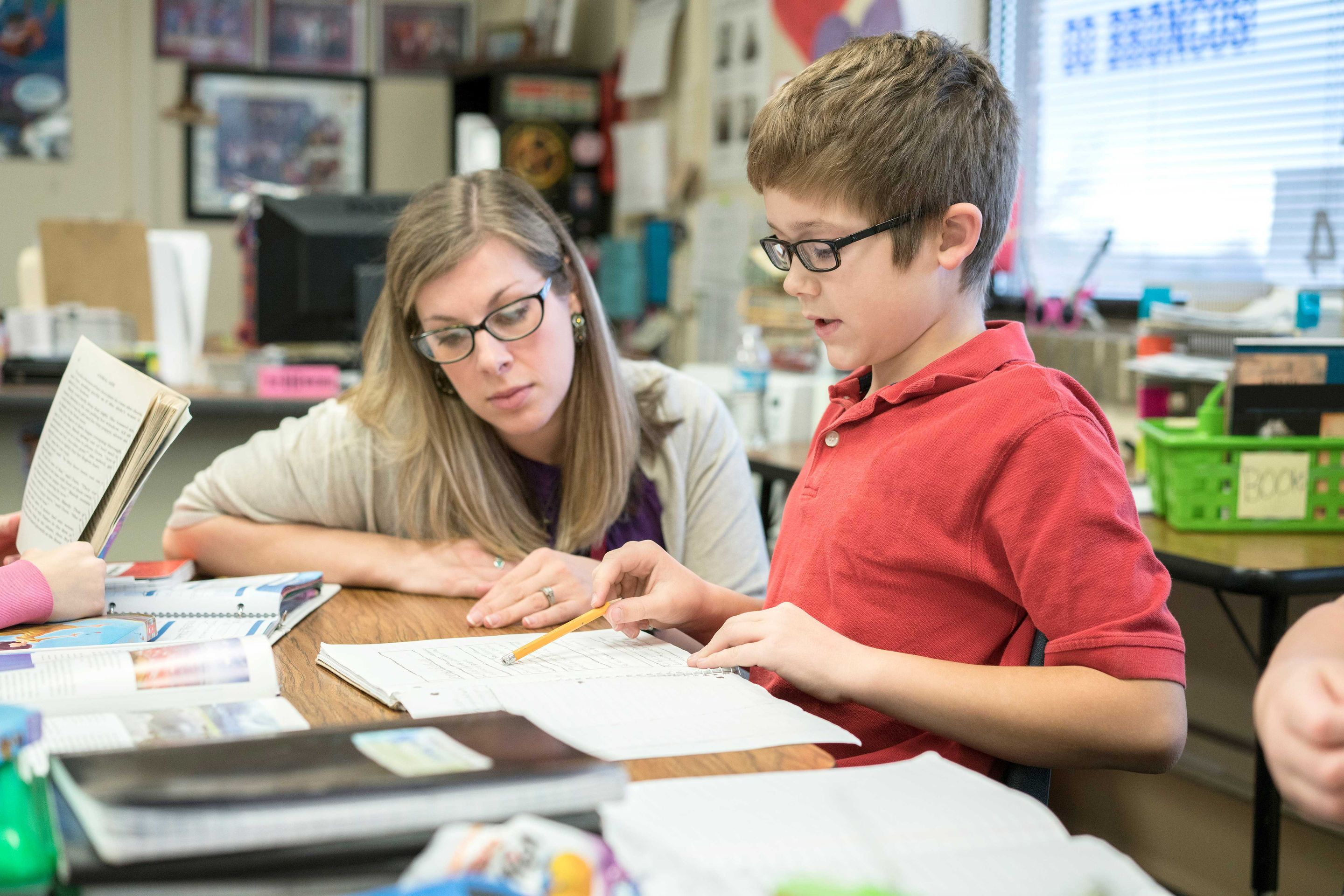 Elementary school teacher helping student in classroom.