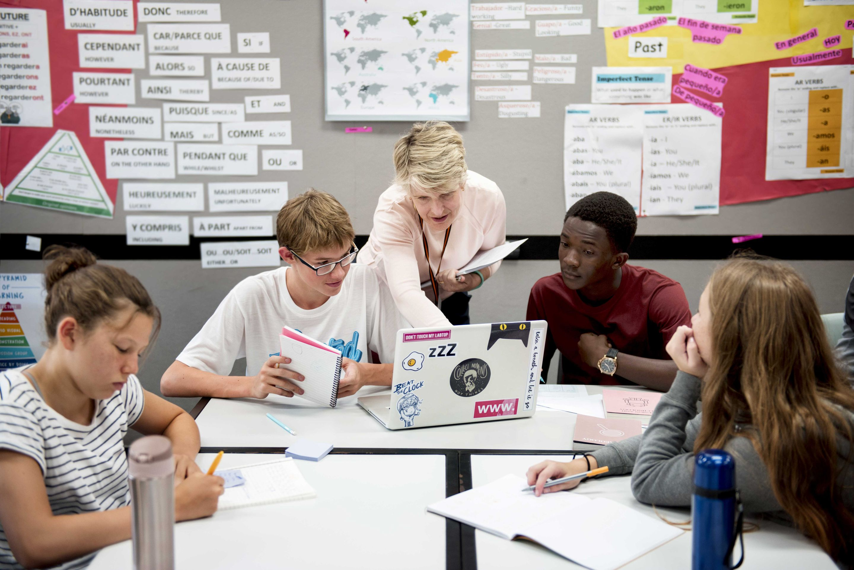 Teacher helping a group of teenage students in the classroom.