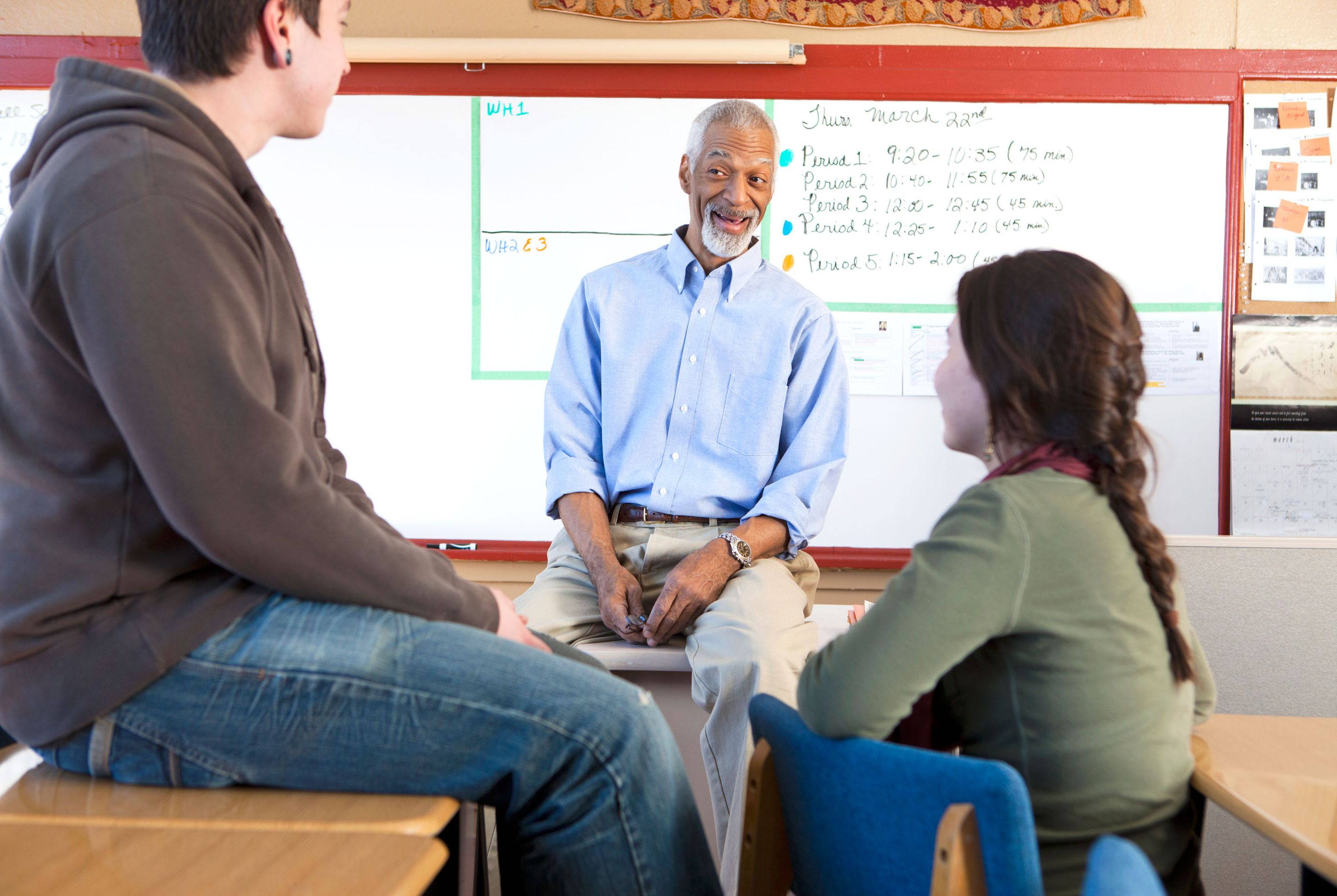 Teacher and students talking in the classroom.