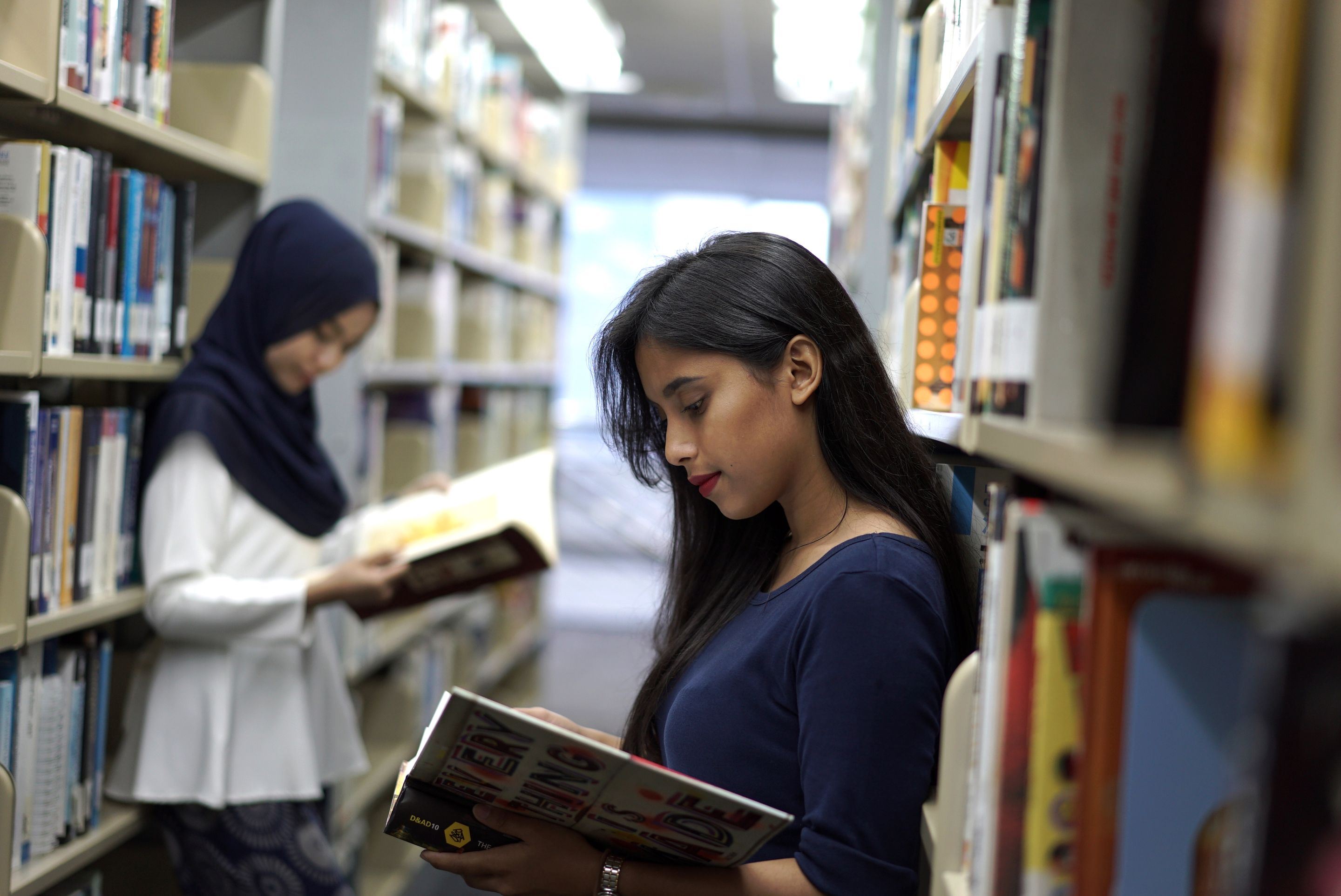 Two high school students reading in the library
