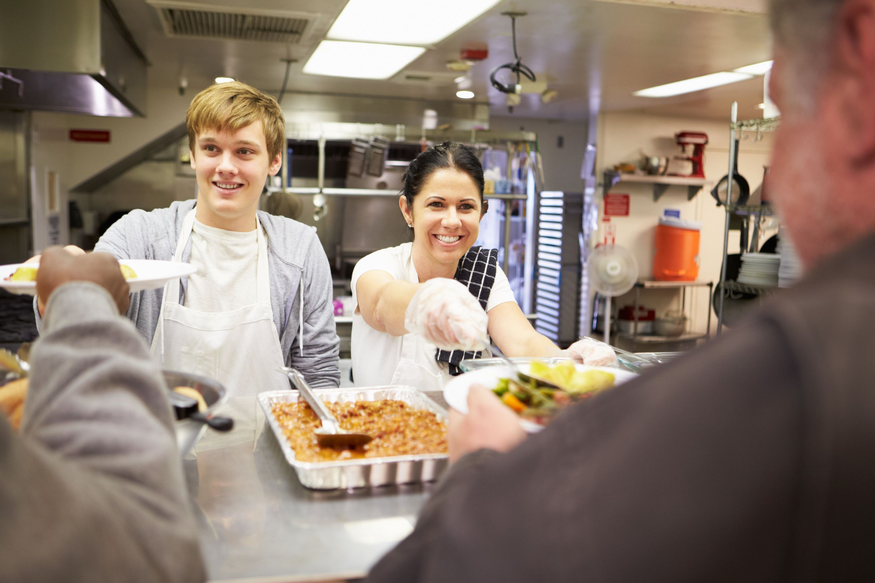 Two students serving free meals to homeless people at a free dining room