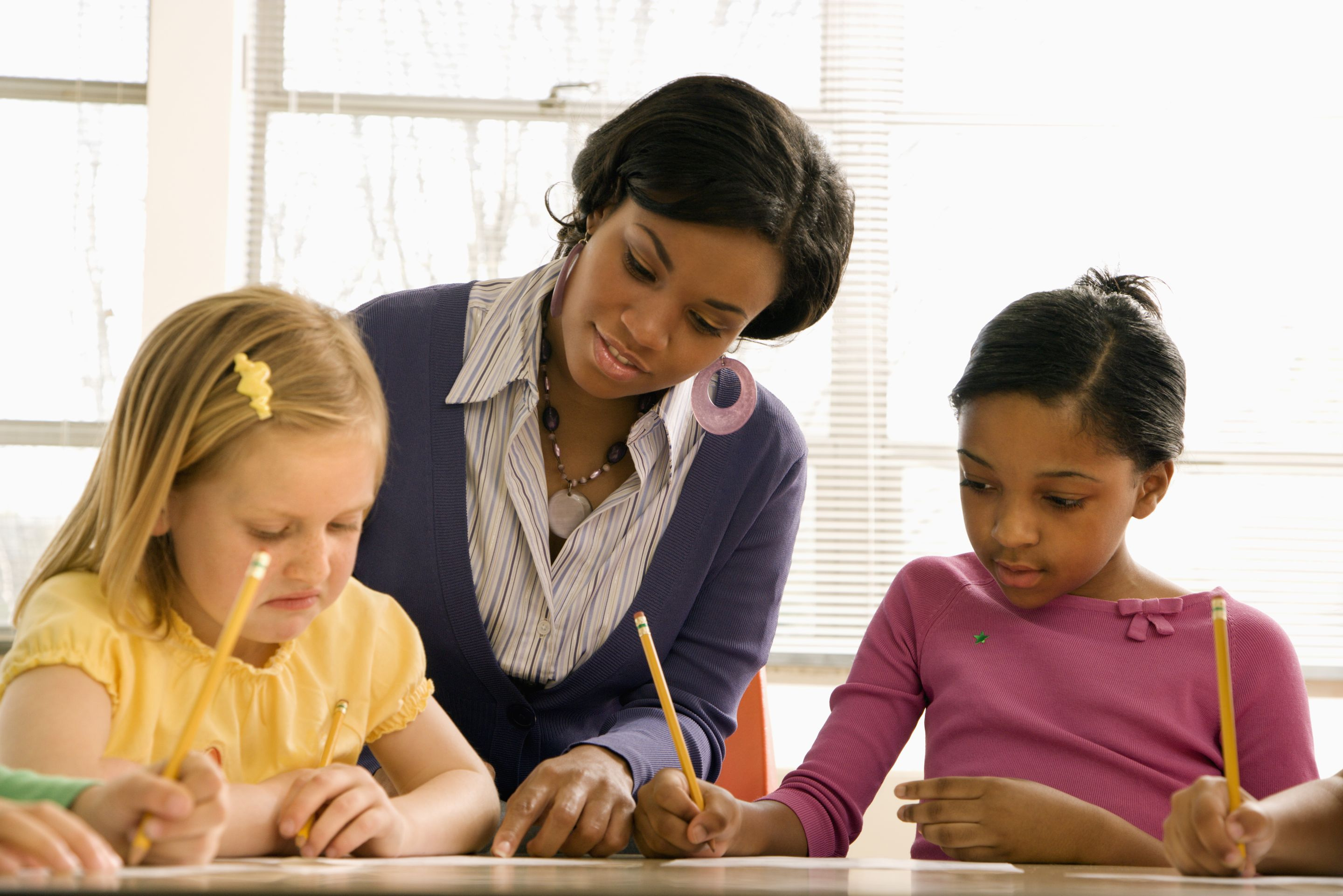 Principal looking over students' shoulders in class, checking their work
