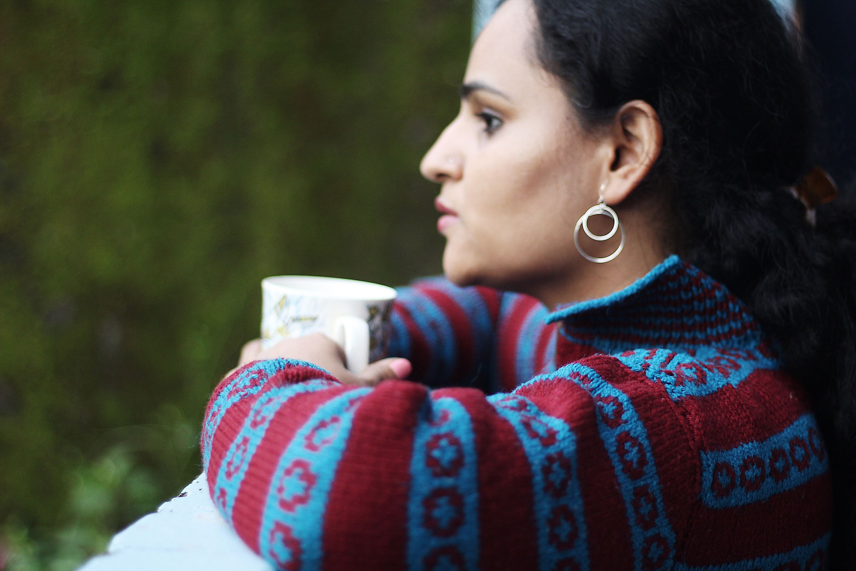 Woman looks thoughtfully out of a window with a cup of coffee in her hand