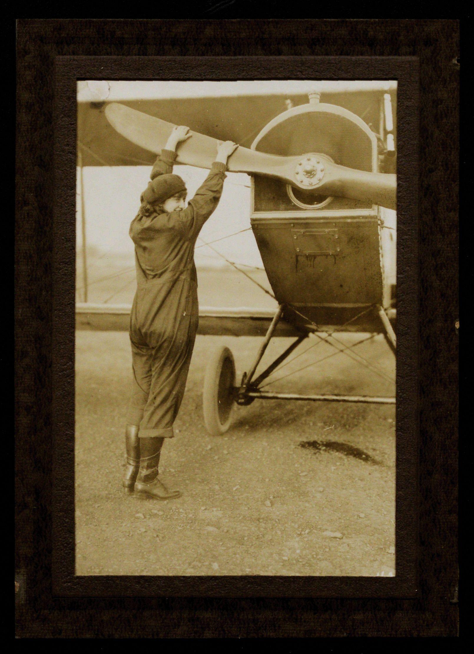 An archival image of Neta Snook, Amelia Earhart's flight instructor, adjusting a plane's propeller in 1920.