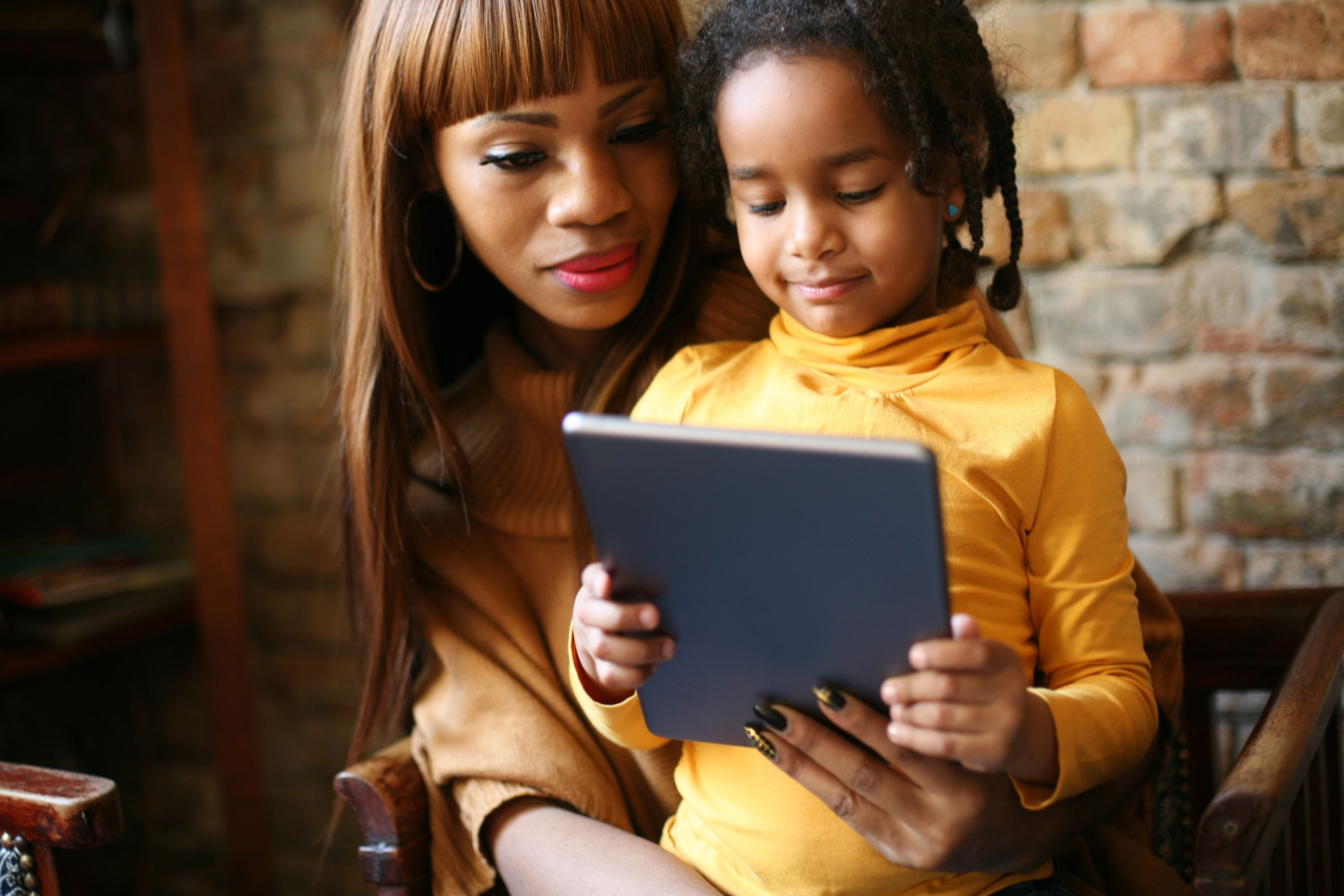 A daughter sitting on her mother's lap, both looking at a tablet that the daughter is holding