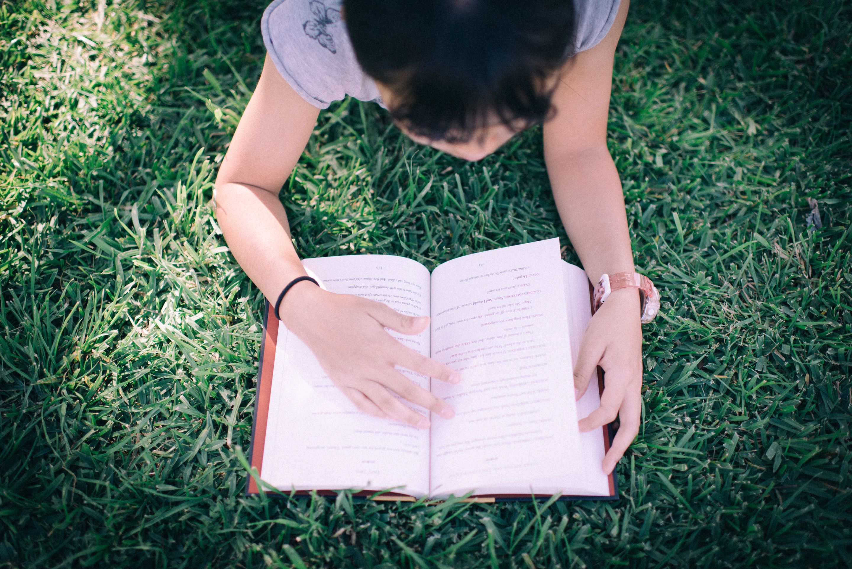 A middle school girl reading a book in a park on the grass