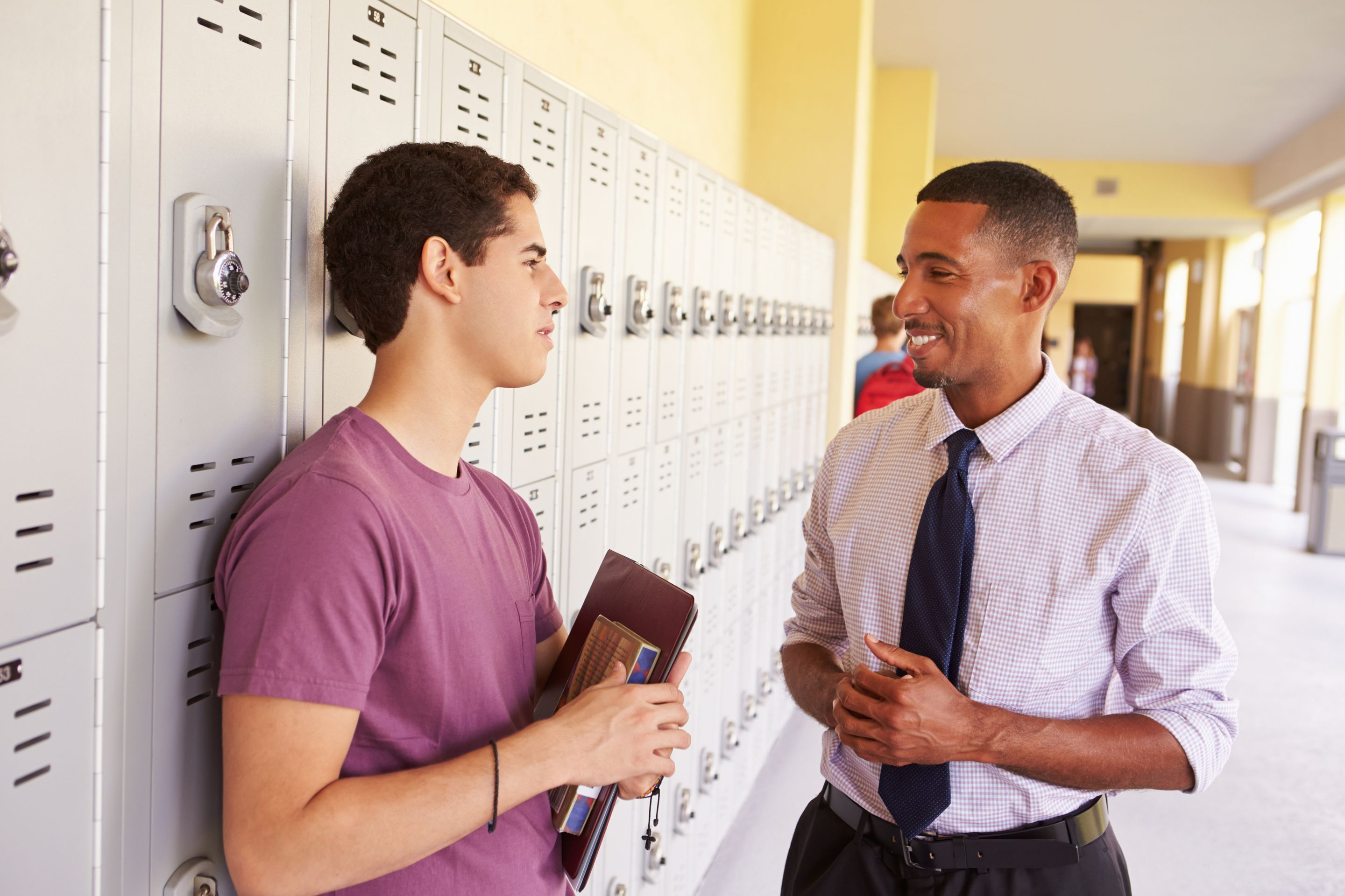 High school teacher talks to a student in the hallway. Both are smiling.