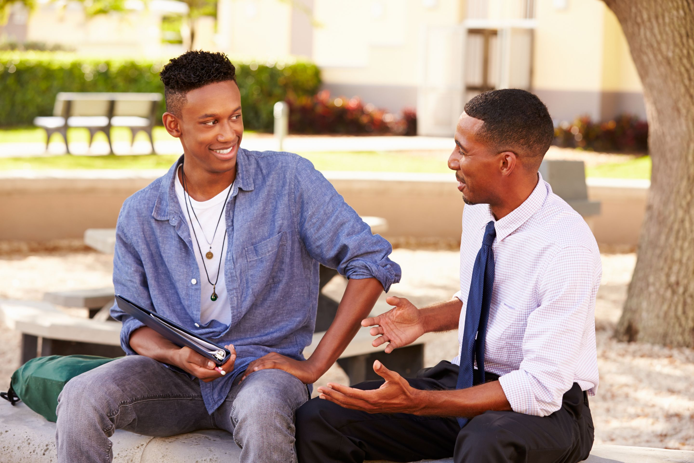 A teacher talking to his student outdoors, both smiling