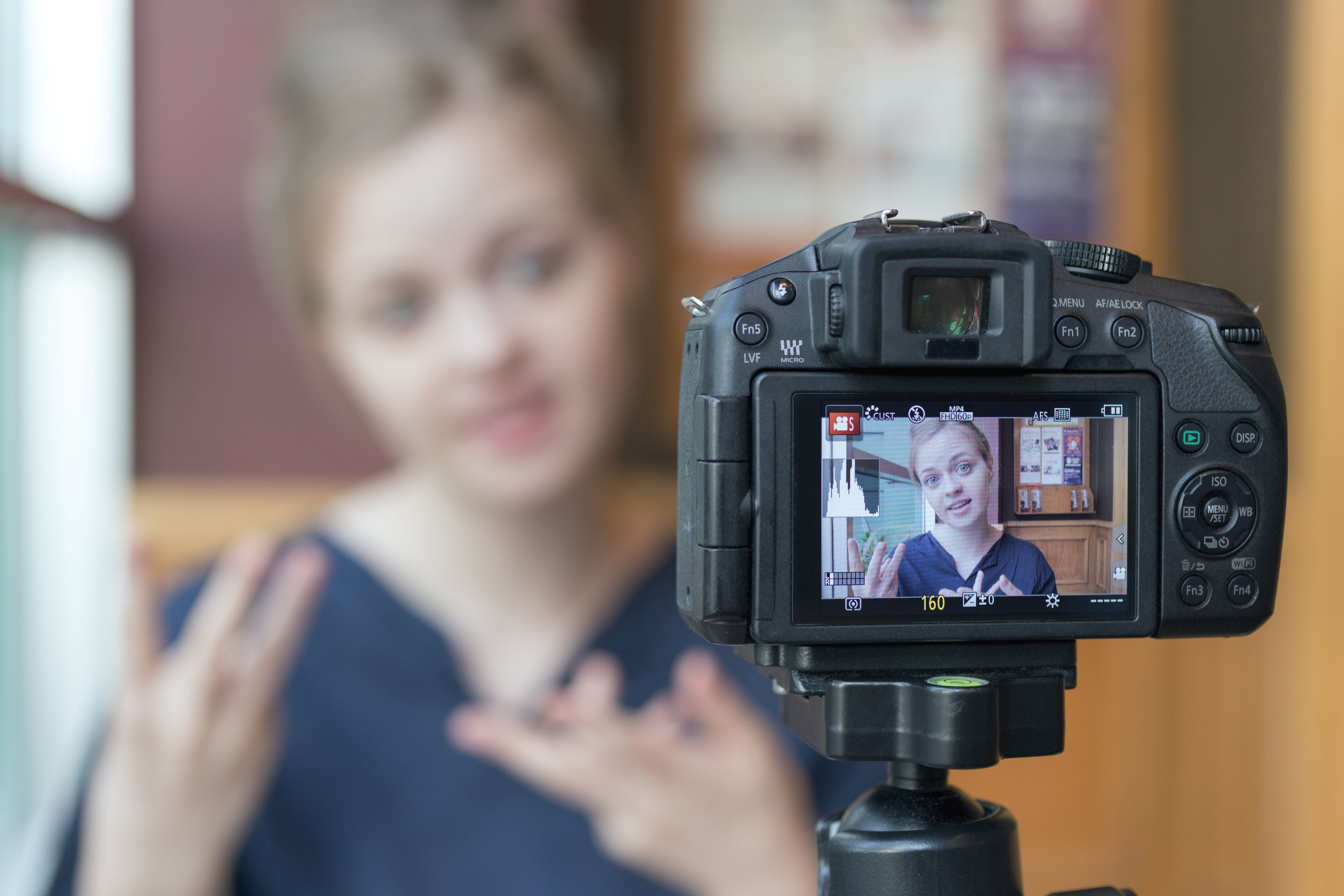 A student filming herself talking on a DSLR camera