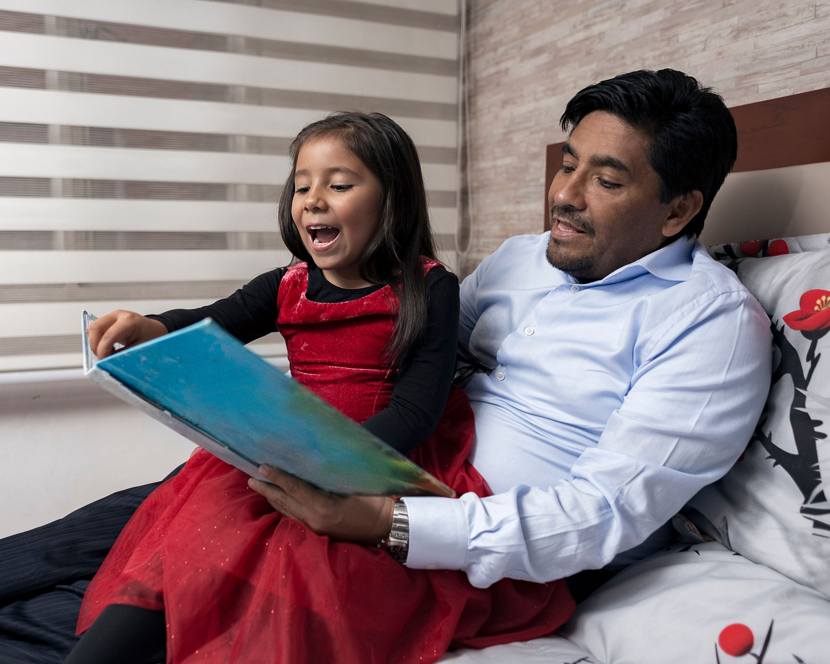 A father reading a picture book with his daughter