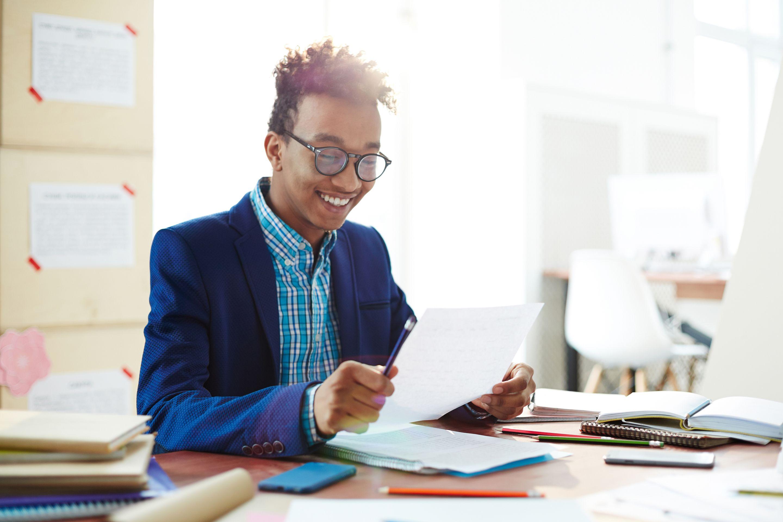 A high school student looking over an essay he has written