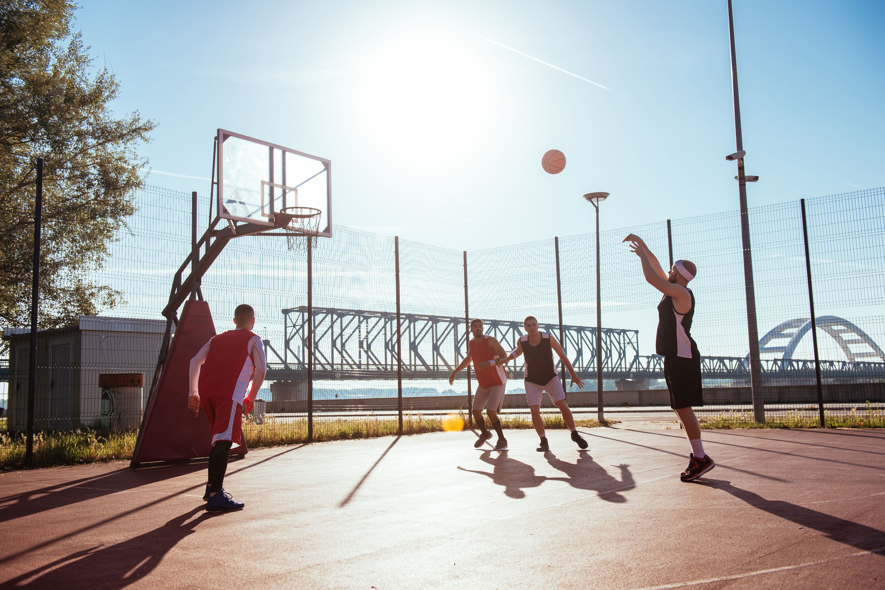Four men playing basketball. One is shooting a free throw.