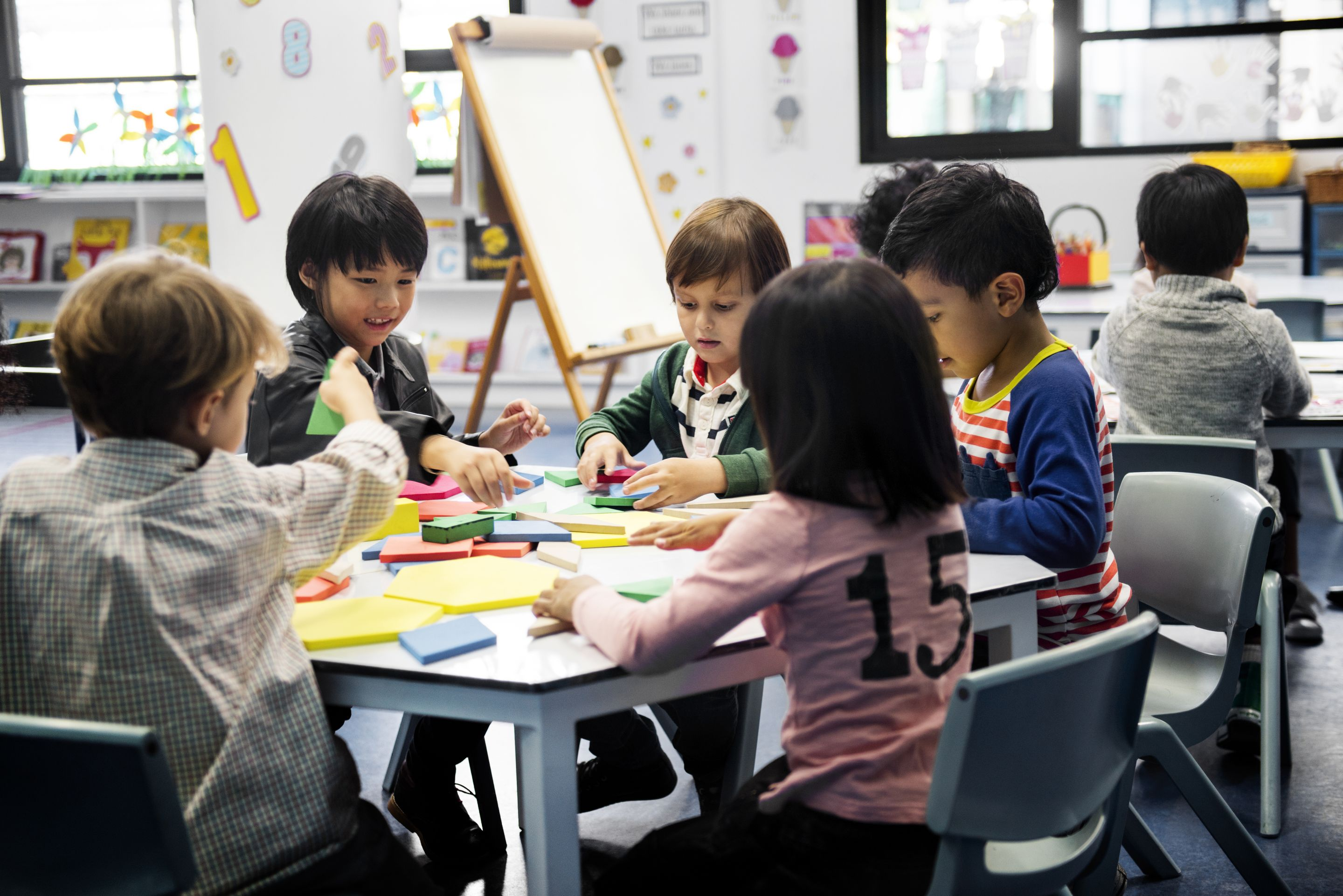 A group of five kindergarten students sitting at a table together, working with blocks in different shapes and sizes