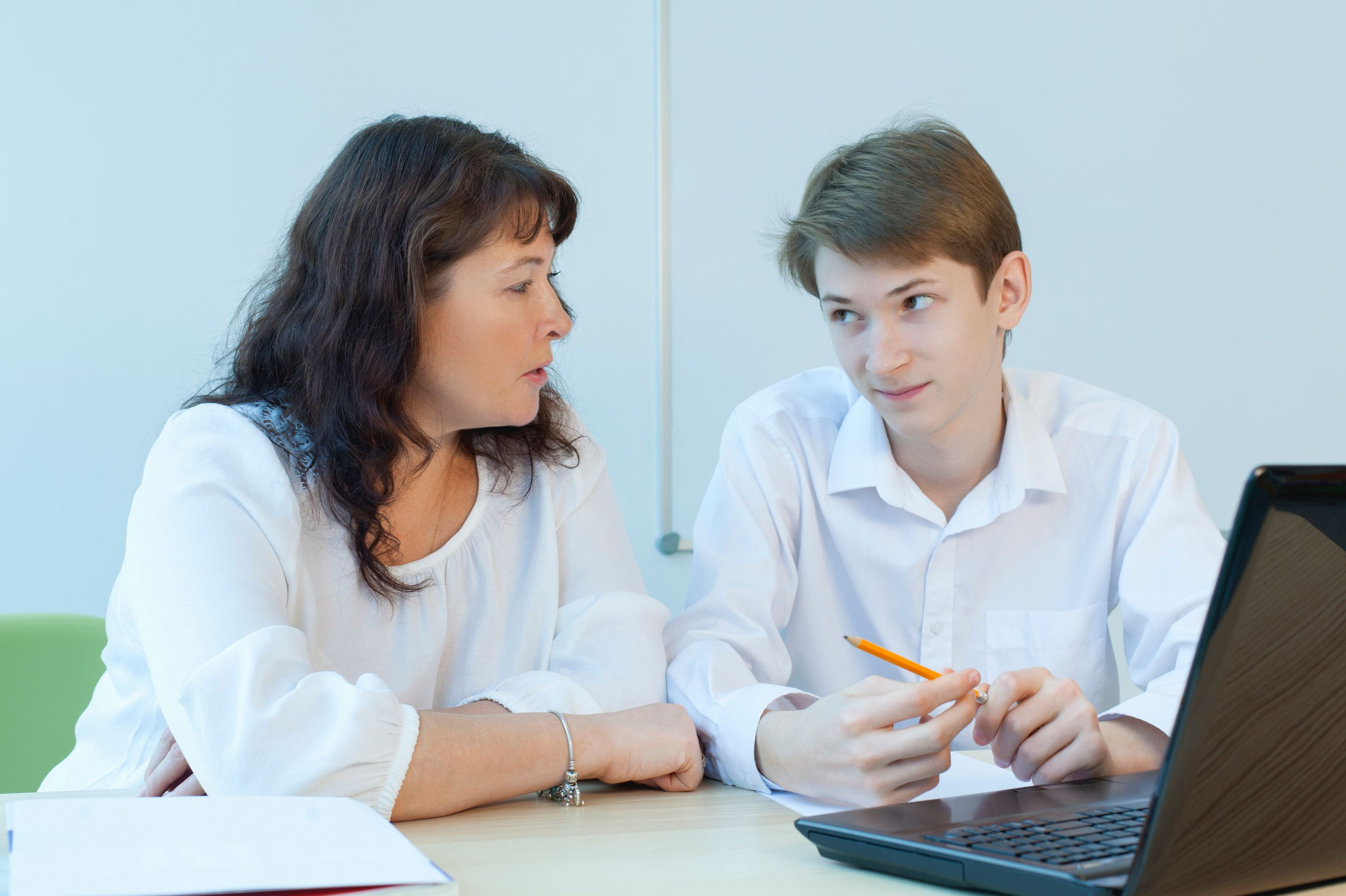 A teacher listens to and comforts a student