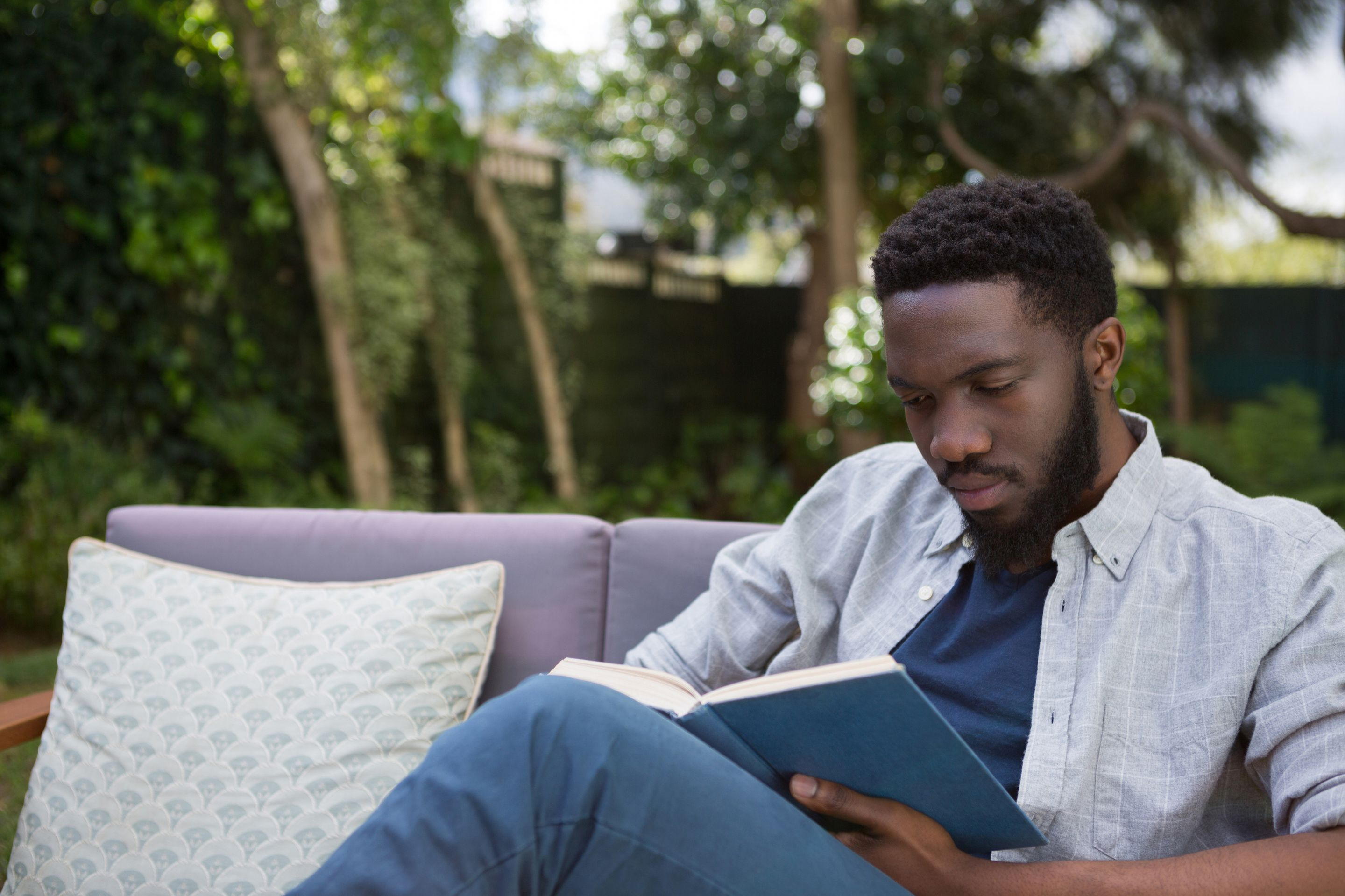 Man reading a book on an outdoor patio